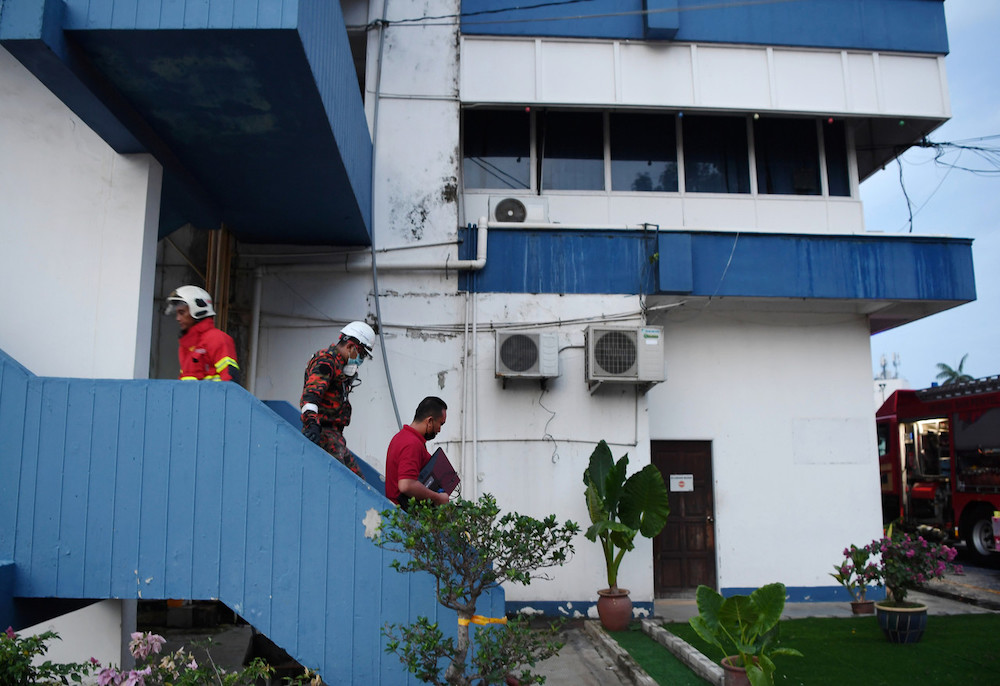 Policemen are seen carrying out computers saved from the fire on the third floor of the Kuantan CID as firemen arrive to control the blaze. June 6, 2021. — Bernama pic