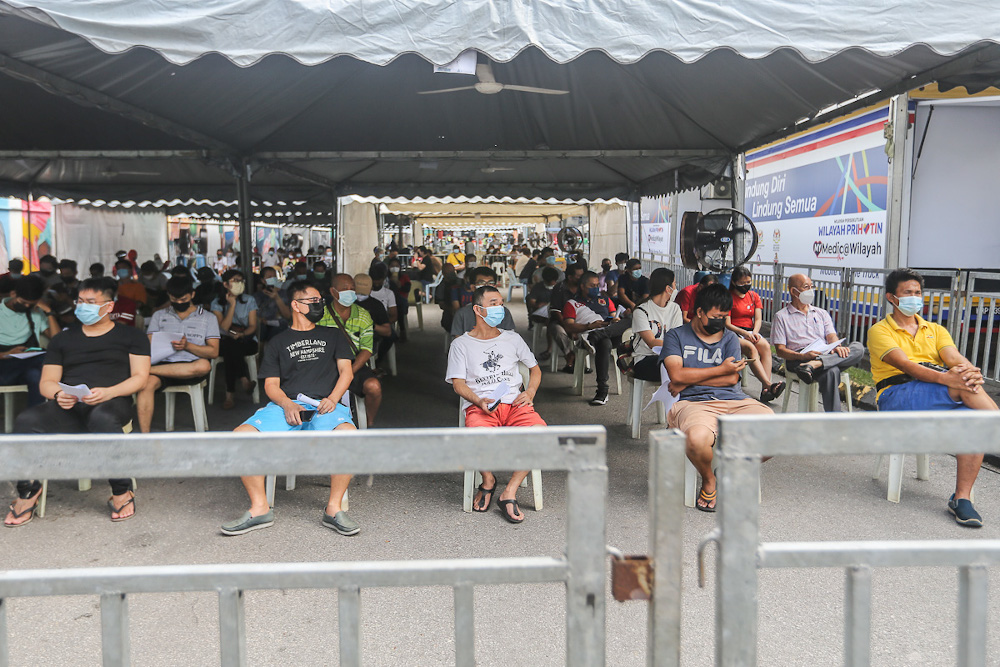 Traders and workers at Pasar Borong Kuala Lumpur queue to receive their Covid-19 vaccination through the MYMedic@Wilayah Vaccine Mobile Truck programme in Selayang June 20, 2021. — Picture by Yusof Mat Isa