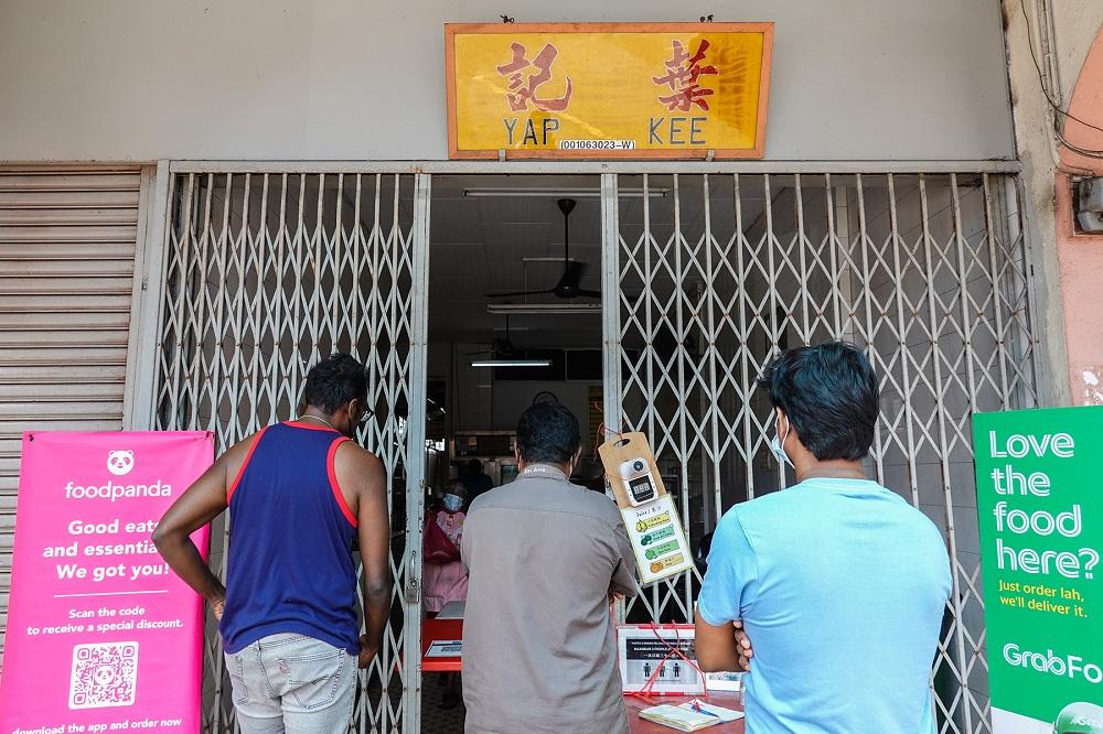 Customers wait at the entrance of Yap Kee kopitiam in Klang June 23, 2021.