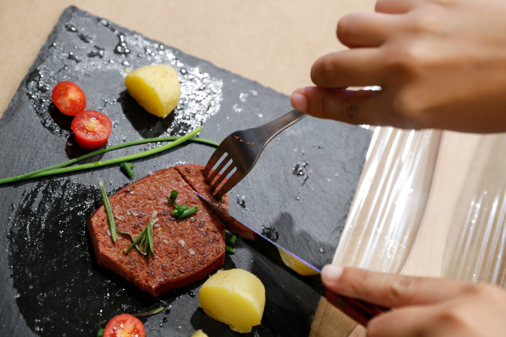 A person cuts a piece of meat printed with a 3D printer by Novameat, during the Mobile World Congress (MWC) in Barcelona, Spain, June 29, 2021. — Reuters pic