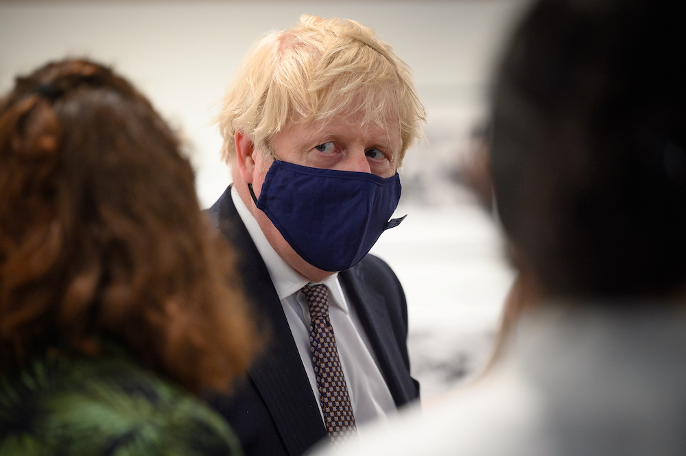British Prime Minister Boris Johnson discusses the foreign aid cap with a member of an engagement group during a visit to Falmouth's Maritime Museum to meet volunteers and to thank them for hosting the media centre for the G7 Summit, in Falmouth, Britai