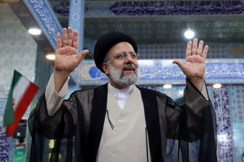 Presidential candidate Ebrahim Raisi gestures after casting his vote during presidential elections at a polling station in Tehran, Iran June 18, 2021. — Reuters pic