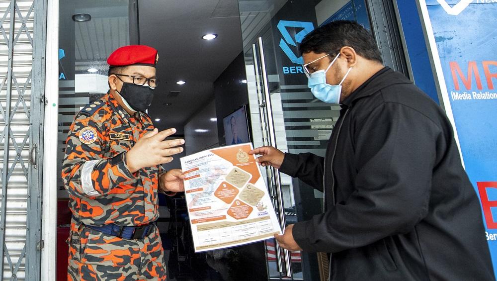 Kelantan Fire and Rescue Department of Malaysia director Zainal Madasin (left) hands a flyer to the Kalantan Barisan Nasional bureau chief Noor Bakhtiar Ahmad in Kota Baru June 9, 2021. — Bernama pic