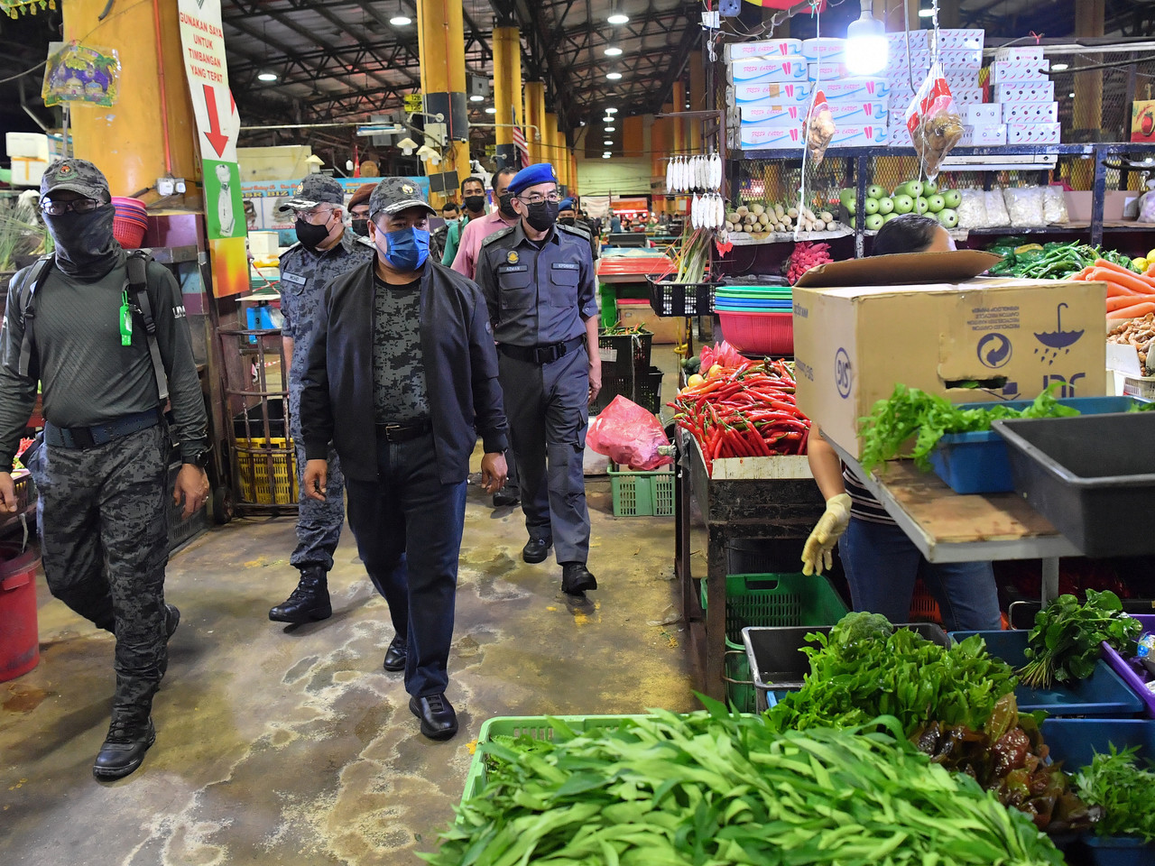 Deputy Home Minister Datuk Seri Ismail Mohamed Said and officers from the Immigration Department inspect the vicinity following a raid at the Selangor Wholesale Market in Serdang June 26, 2021. — Bernama pic