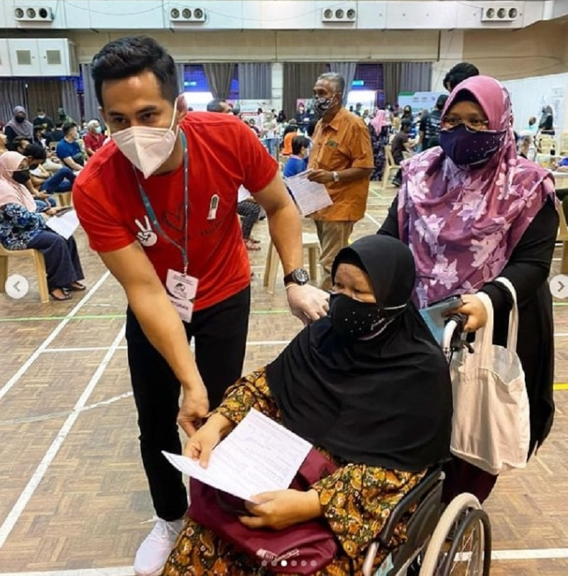 Fizo (in red) helping a senior citizen at UKM's Covid-19 vaccination centre. — Picture via instagram/fizoomar
