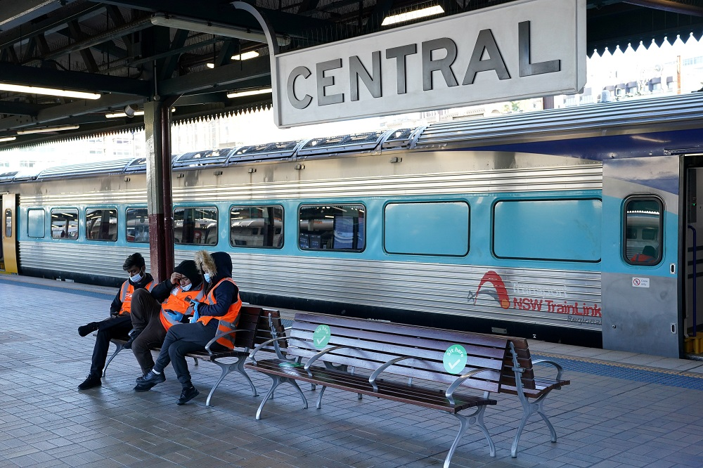 Transport workers sit together on a train platform devoid of passengers at Central Station in Sydney, Australia June 26, 2021. ― Reuters pic