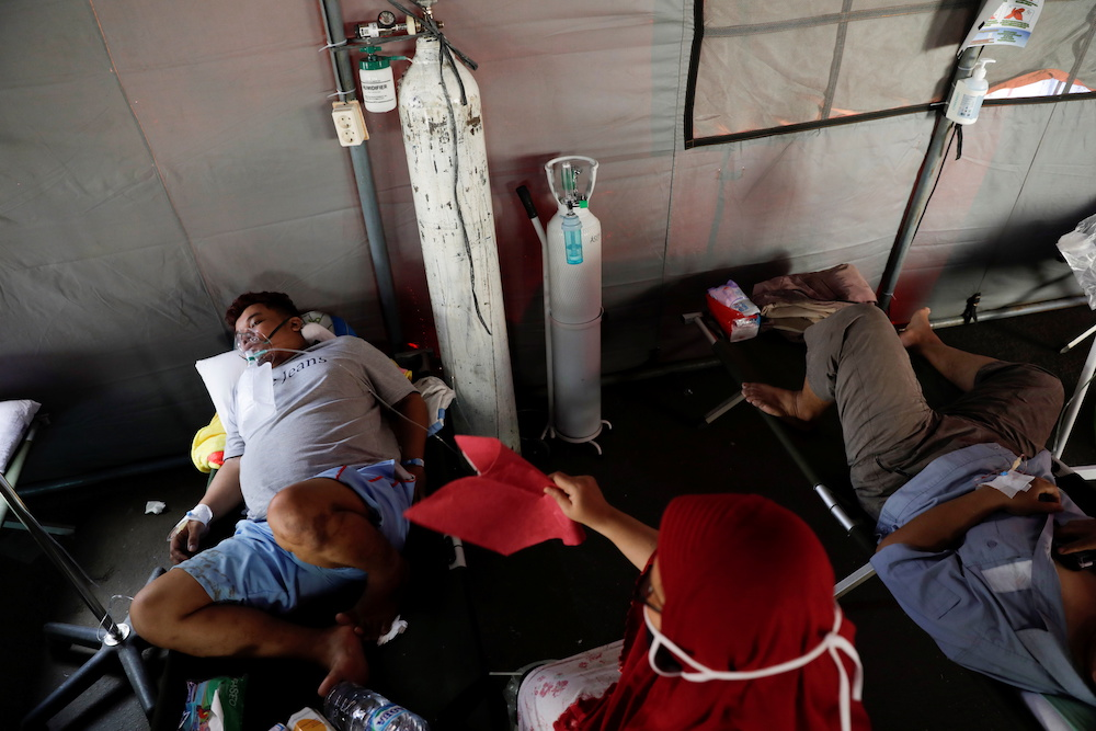 A 34-year-old patient suffering from Covid-19 rests at a temporary tent outside the emergency ward of a government hospital in Bekasi, on the outskirts of Jakarta, Indonesia, June 25, 2021. — Reuters pic