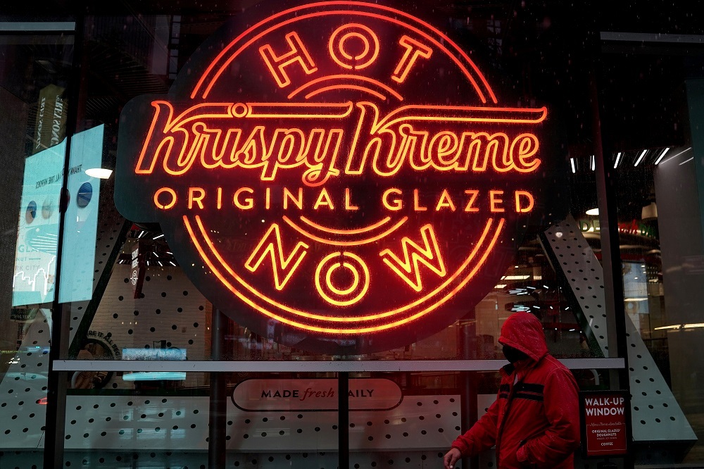 A man walks past a Krispy Kreme 'Hot Now' neon sign in Times Square in the Manhattan borough of New York October 16, 2020. ― Reuters file pic