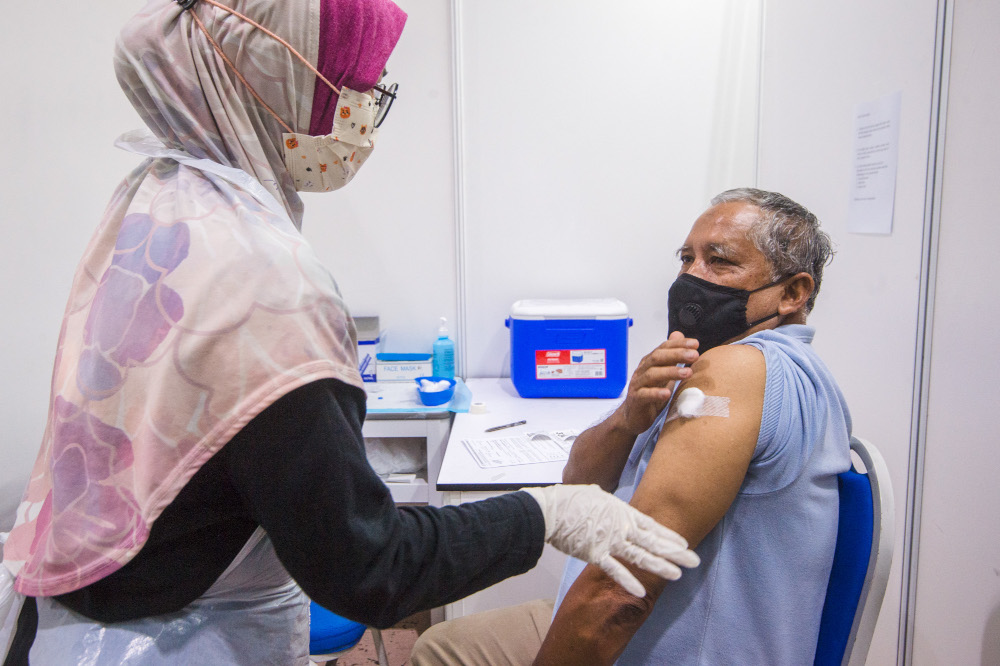 People receive their jabs at the Covid-19 vaccination centre at the Mines International Exhibition and Convention Centre, Seri Kembangan, June 17, 2021. — Picture by Shafwan Zaidon