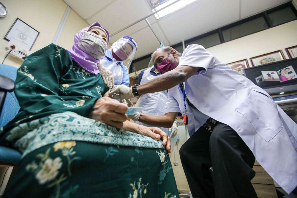 A senior citizen receives a dose of the Covid-19 vaccine at a clinic under the Perak Medical Centre Group of Clinics in Ipoh June 15, 2021. — Picture by Farhan Najib