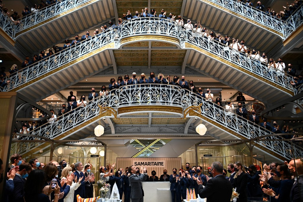 French President Emmanuel Macron (centre) and employees of Paris' Iconic department store La Samaritaine applaud during a ceremony marking the store's reopening after 16 years of closure, on June 21, 2021 in Paris. — AFP pic