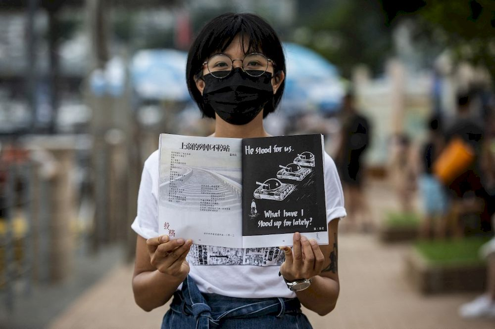 This picture taken on June 2, 2021 shows district councillor Debby Chan, who said she plans to mourn the 1989 Tiananmen Square crackdown by holding a poetry reading and sharing session with residents in her neighbourhood, holding a magazine of poetry in Hong Kong. — AFP pic