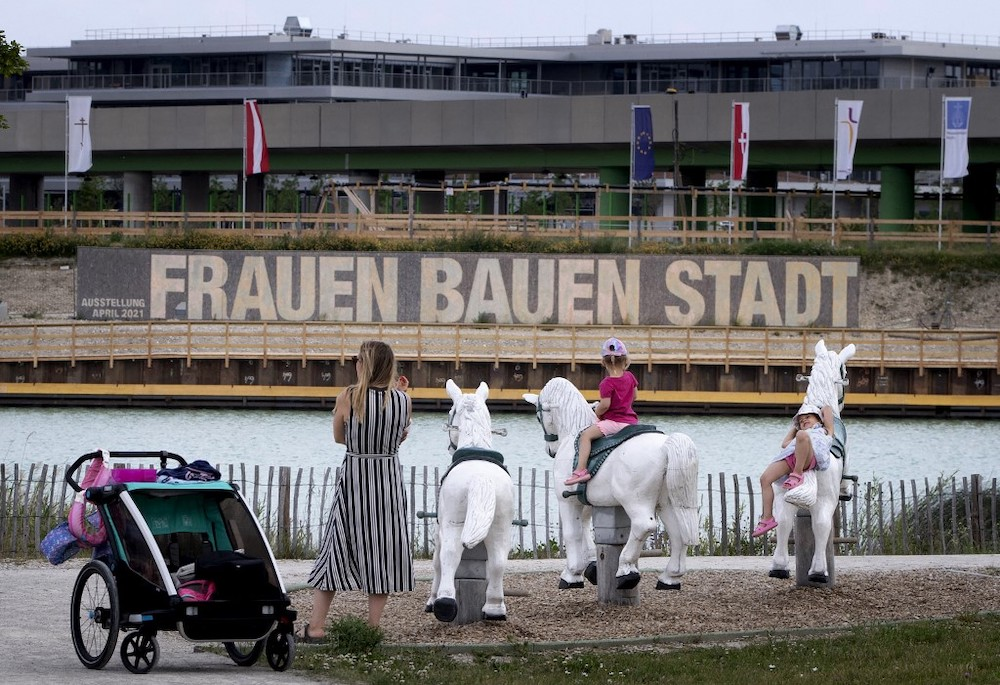 Children play in a playground facing large panels proclaiming the slogan 'Women build the city' next to some of the building sites that will eventually contain 12,000 new housing units, at Vienna's suburb Seestadt, Austria, on June 8, 2021. — AFP pi