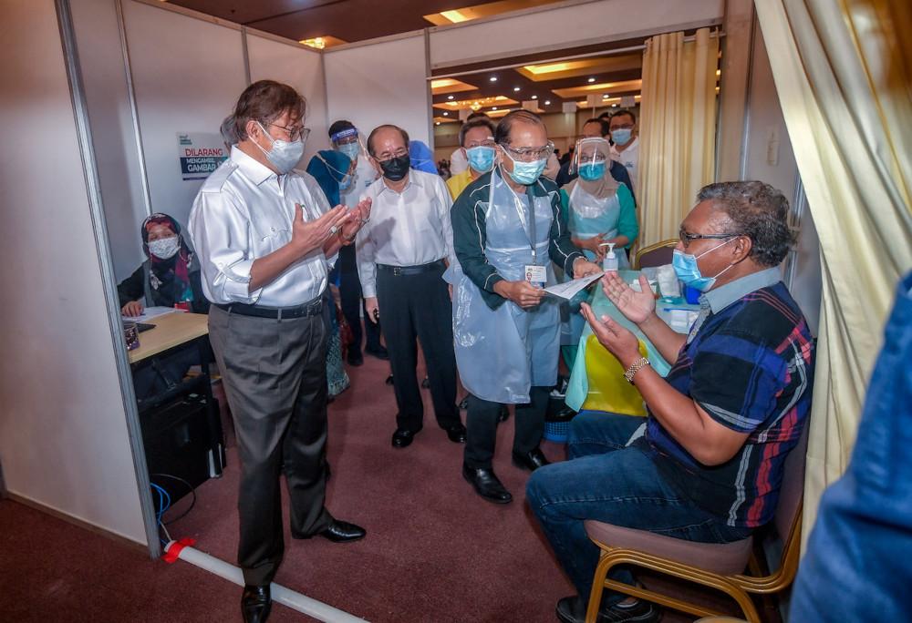 Chief Minister Datuk Patinggi Abang Johari Openg with a vaccine recipient at Universiti Malaysia Sarawak's Covid-19 vaccination centre in Kuching, June 18, 2021. — Bernama pic
