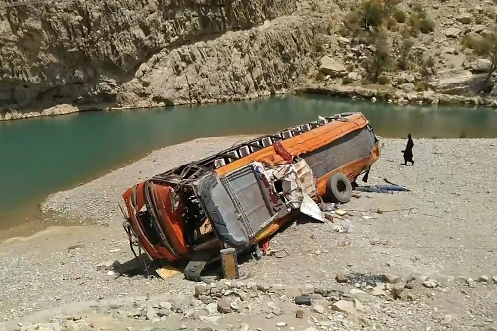 A man walks past a damaged bus at the site of an accident in a remote district of Balochistan province on June 11, 2021. A bus carrying dozens of pilgrims plunged into a ravine in southwest Pakistan on June 11 killing at least 18 passengers, officials said. — AFP pic