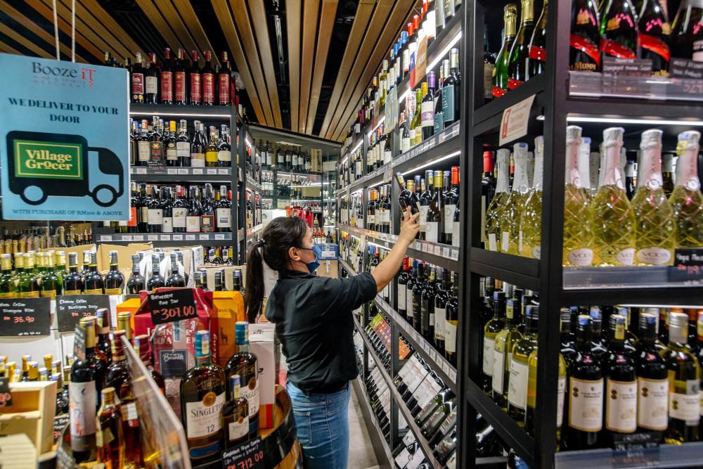 Staff arranging bottles of alcohol at Village Grocer in Bangsar, Kuala Lumpur, June 4, 2021. — Picture by Firdaus Latif