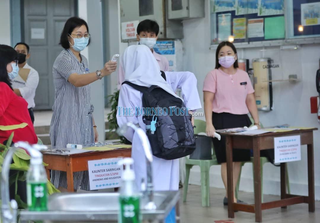 A teacher checking the body temperature of a student. ― Borneo Post pic