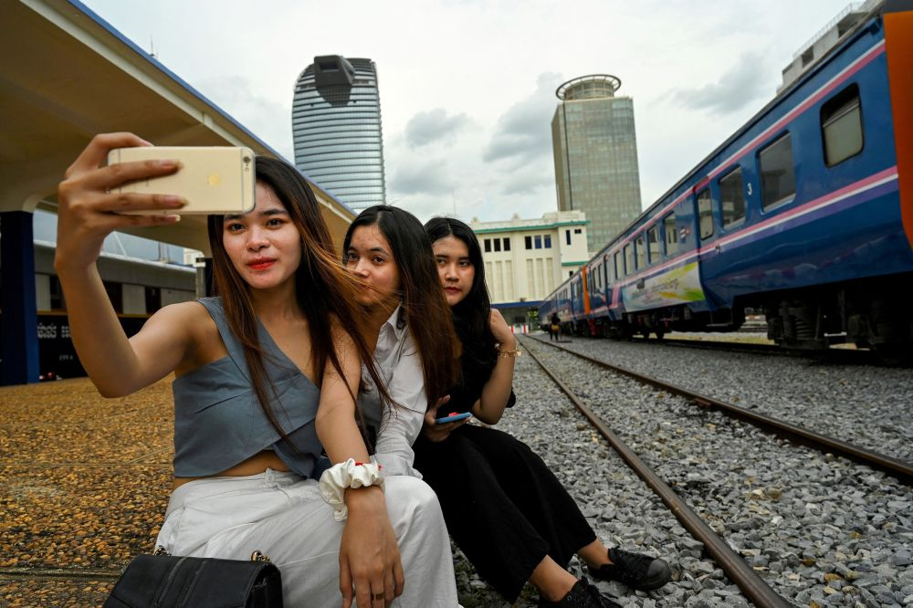 Women posing for a selfie next to a train at a railway station in Phnom Penh. — ETX Studio pic
