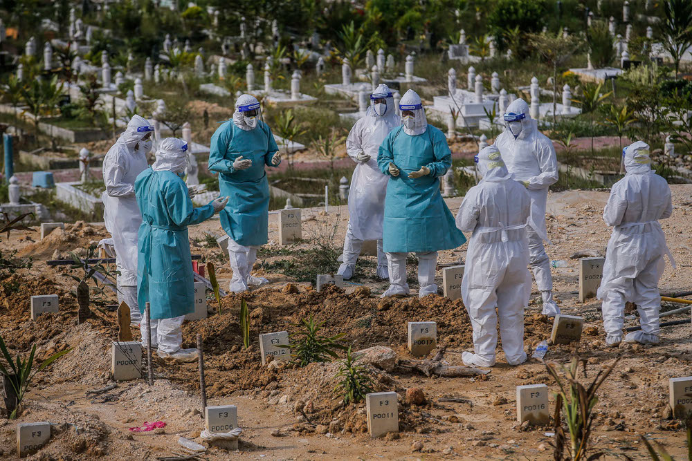 Workers wearing personal protective equipment recite a prayer after burying a person who died from Covid-19 at the Muslim cemetery in Gombak June 8, 2021. ― Picture by Hari Anggara