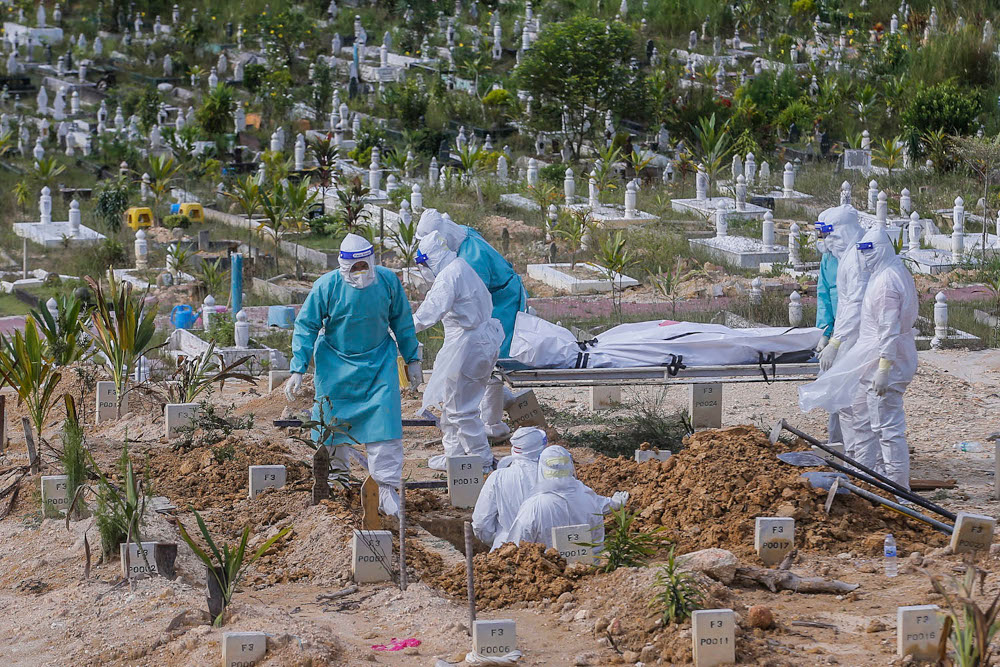 Health workers in personal protective equipment prepare to bury the body of a Covid-19 victim at the Muslim cemetery in Gombak June 8, 2021. ― Picture by Hari Anggara