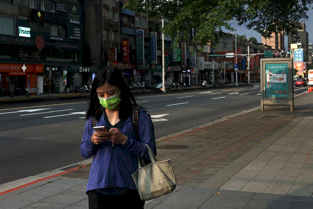 A woman uses her phone while wearing a protective mask following the recent rise in the Coronavirus disease (Covid-19) infections in Taipei, Taiwan May 23, 2021. — Reuters pic
