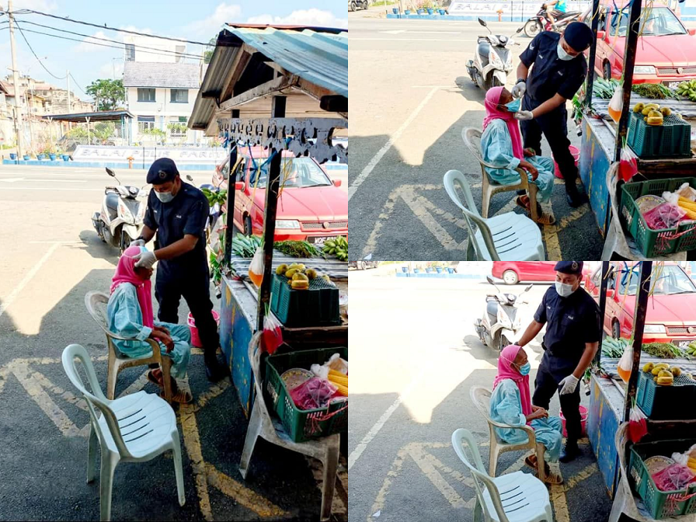 A Perak policeman officer was applauded for helping an elderly lady put on her face mask after she had forgotten to wear one. ― Picture courtesy of Facebook/Sas Barakah