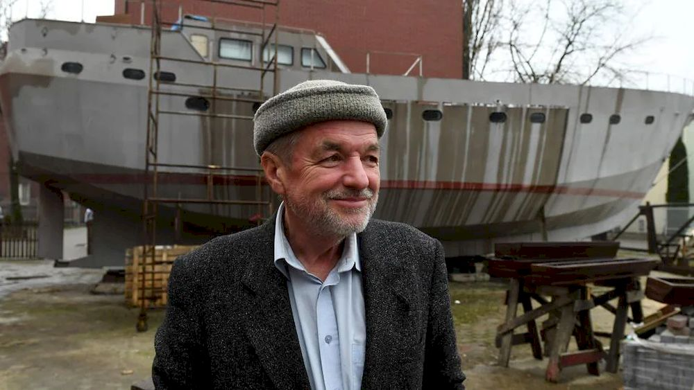 Ship Captain Waldemar Rzeznicki stands in front of a steel schooner called 'Father Boguslaw' under construction at the courtyard of a homeless shelter run by Catholic Fathers in Warsaw on March 27, 2021. — AFP pic