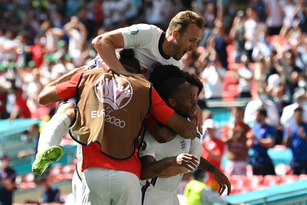 England forward Raheem Sterling celebrates scoring his team's first goal with forward Harry Kane and teammates during the Uefa Euro 2020 Group D football match between England and Croatia at Wembley Stadium in London June 13, 2021. — AFP pic