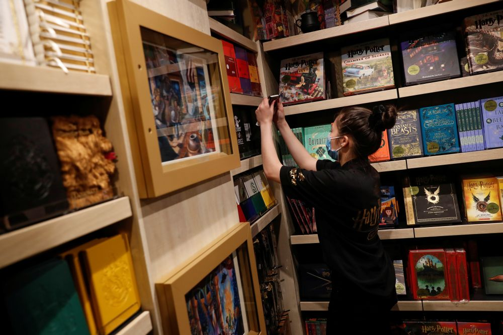 An employee of the Harry Potter New York store pulls a book from a shelf during press preview in the Flatiron district of New York City May 28, 2021. — Reuters pic