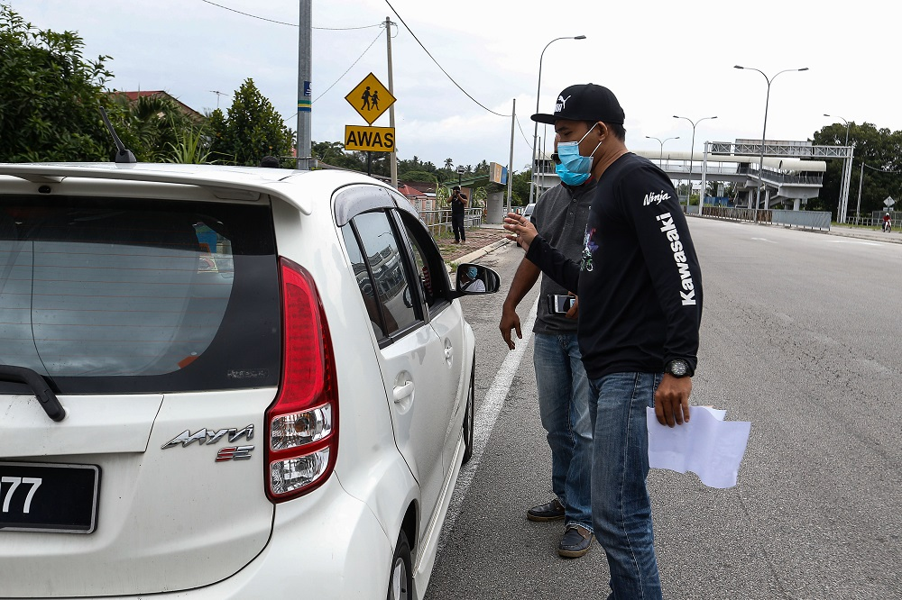 An undercover RTD officer questions a driver suspected of illegally ferrying passengers near Kampung Valdor in Jawi June 29, 2021. ― Picture by Sayuti Zainudin