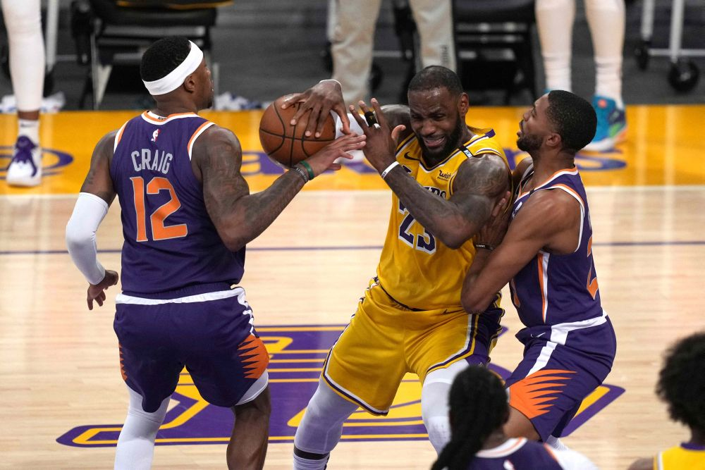 Los Angeles Lakers forward LeBron James (23) battles for the ball with Phoenix Suns' Torrey Craig (12) and Mikal Bridges (25) in the first half during game six in the first round of the 2021 NBA Playoffs at Staples Centre June 3, 2021. — Reuters pic