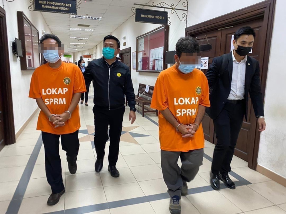 The two suspects leave the courtroom after they were ordered to be remanded until Monday. — Borneo Post Online pic
