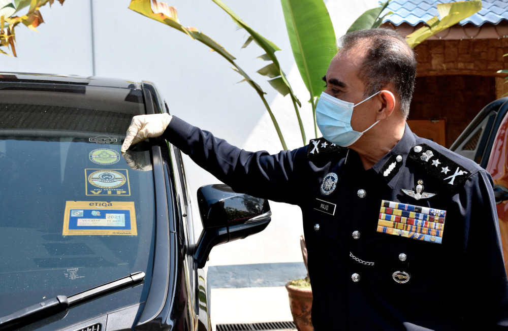 Melaka police chief Datuk Abdul Majid Mohd Ali showing the car stickers resembling the Royal Malaysia Police logo used on a vehicle by Gang 36 members at a press conference in Melaka, June 11, 2021. — Bernama pic