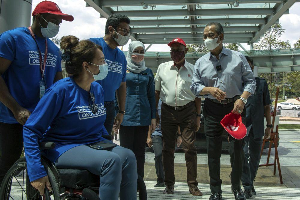Prime Minister Muhyiddin Yassin greets members of the public at the Menara Sime Darby Plantation drive-thru vaccination centre in Petaling Jaya June 24, 2021. — Bernama pic