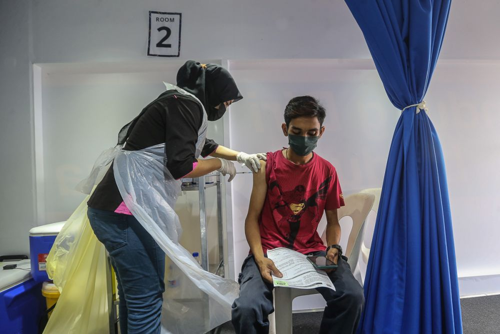 People receive their Covid-19 vaccination through the MYMedic@Wilayah Vaccine Mobile Truck programme at PPR Seri Alam in Kuala Lumpur June 23, 2021. — Picture by Yusof Mat Isa