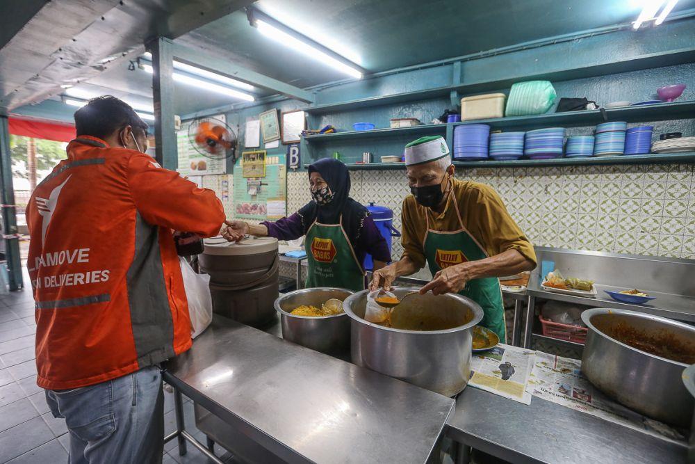 Khamis Majid packs food for a customer at Restoran Noor in Kuala Lumpur June 14, 2021. — Picture by Yusof Mat Isa