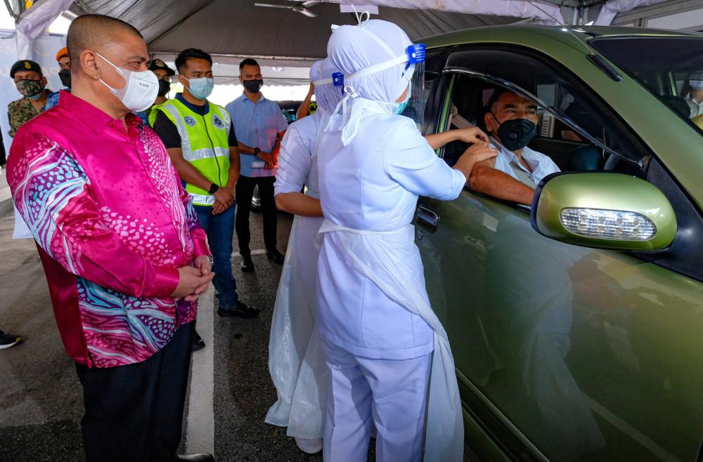 Perak Mentri Besar Datuk Saarani Mohamad observes the drive-through vaccination process at Indera Mulia Stadium in Ipoh, June 10, 2021. — Bernama pic