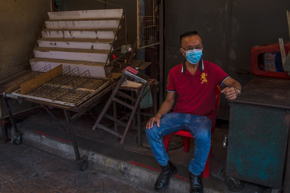 Foo Meng Kin is seen here sitting at one of the closed stalls in Petaling Street. — Picture by Shafwan Zaidon