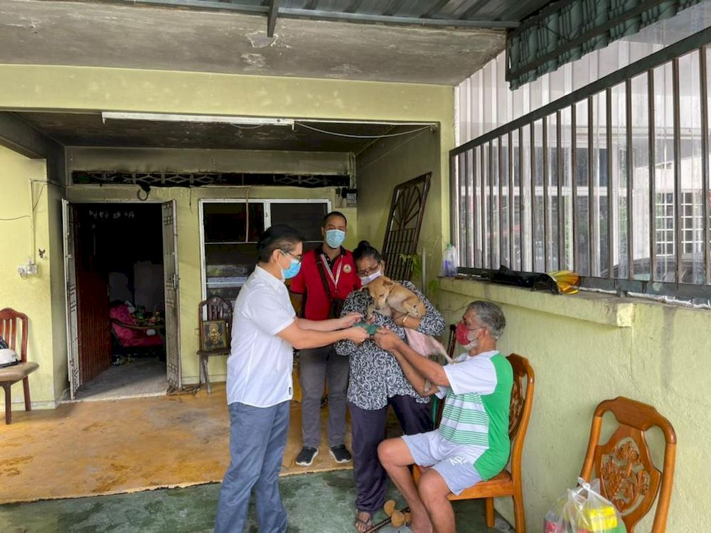 Pasir Bedamar assemblyman Terence Naidu presenting financial aid and provisions to N. Marimuthu whose house at Eastern Garden had been destroyed in an early morning fire on Wednesday. The family was saved from the fire by Anandaveli the dog. — Courtesy photo from Terence Naidu