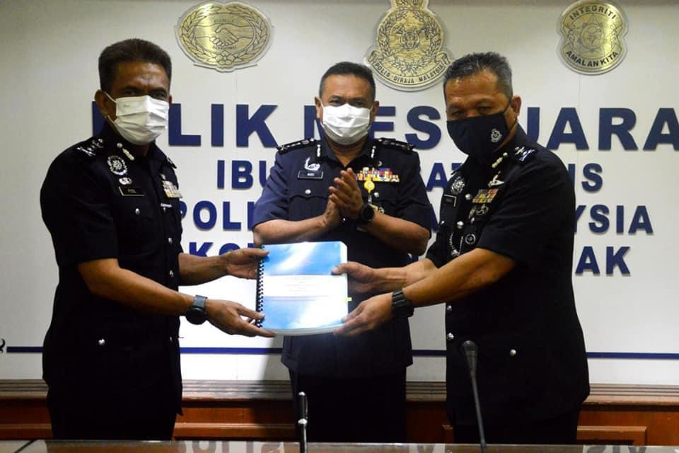 DCP Mancha Ata (right) exchanging documents with Fisol during the ceremony, witnessed by Sarawak Police Commissioner Datuk Aidi Ismail (centre). ― Borneo Post pic