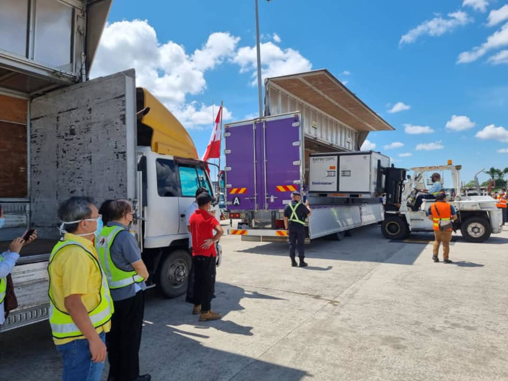 Dr Sim (left) and Uggah (second left) look on as the container containing the Sinovac vaccines is placed onto the truck. — Picture from Facebook/Dr Sim Hui Kian