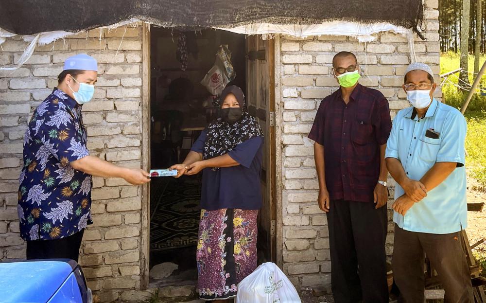 Single mum Rohayah Che Samah receives financial aid and food from Pengkalan Chepa Member of Parliament Muhammad Abdul Munib Zakaria in Kota Baru, June 30, 2021. — Bernama pic
