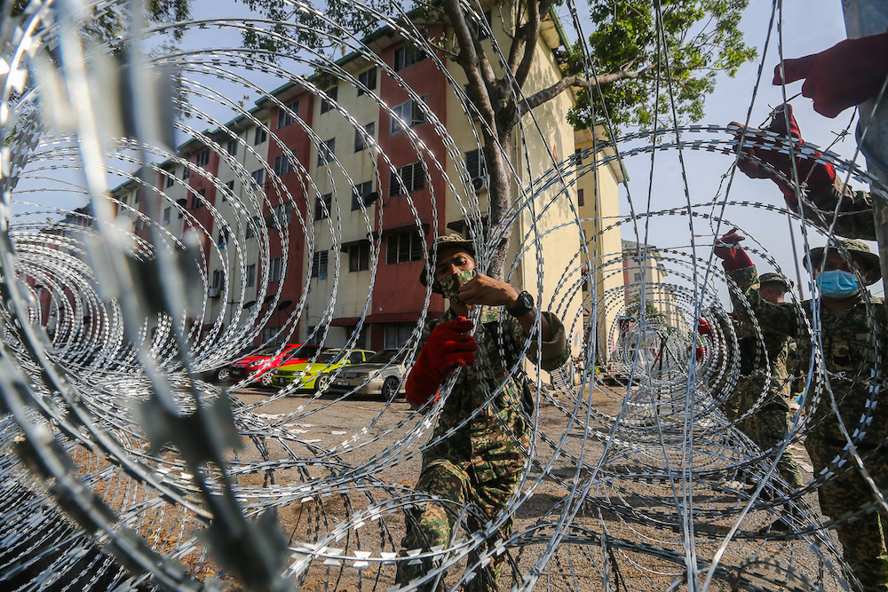 Armed Forces personnel install barbed wire fencing at Pangsapuri Bandar Bukit Tinggi 1, Jalan Nilam 15 during the enhanced movement control order (EMCO) in Klang July 18, 2021. — Picture by Yusof Mat Isa