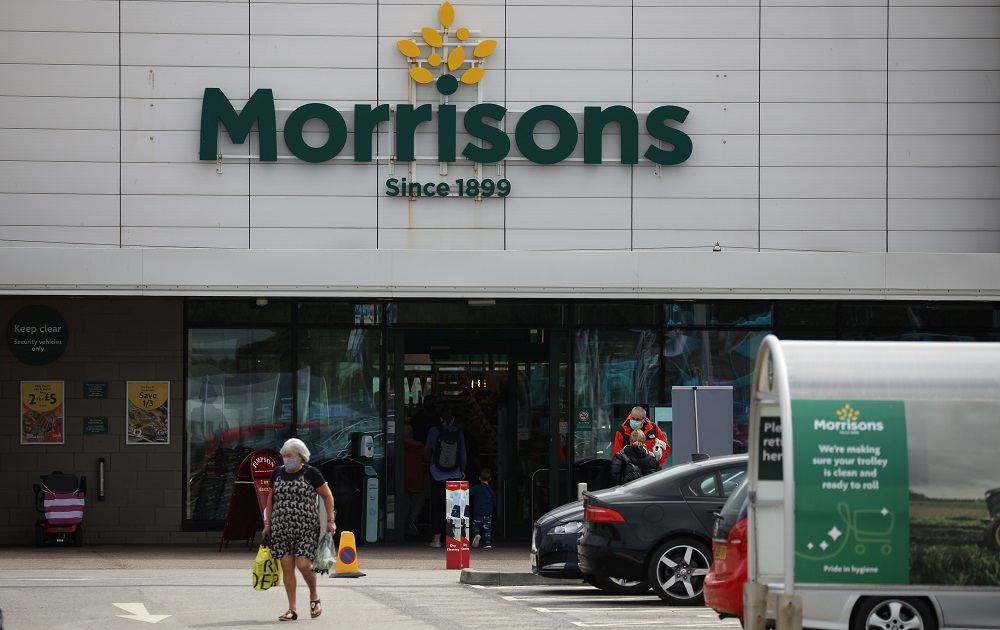 A customer carries a shopping bag outside a Morrisons supermarket in New Brighton, Britain July 5, 2021. — Reuters pic
