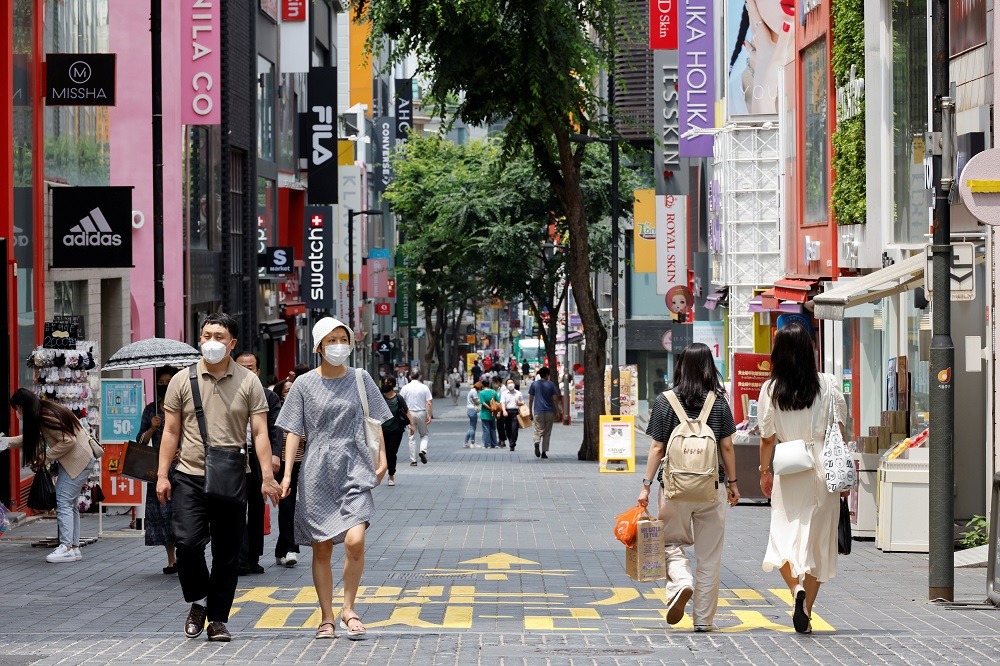 People wearing masks walk in a shopping district amid the coronavirus disease pandemic in Seoul July 9, 2021. — Reuters pic