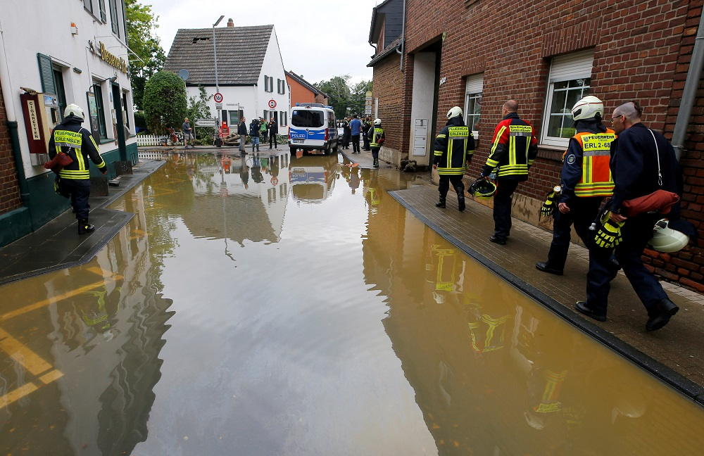 File photo of firefighters walking a flooded street following heavy rainfalls in Erftstadt-Blessem, Germany July 16, 2021. — Reuters pic