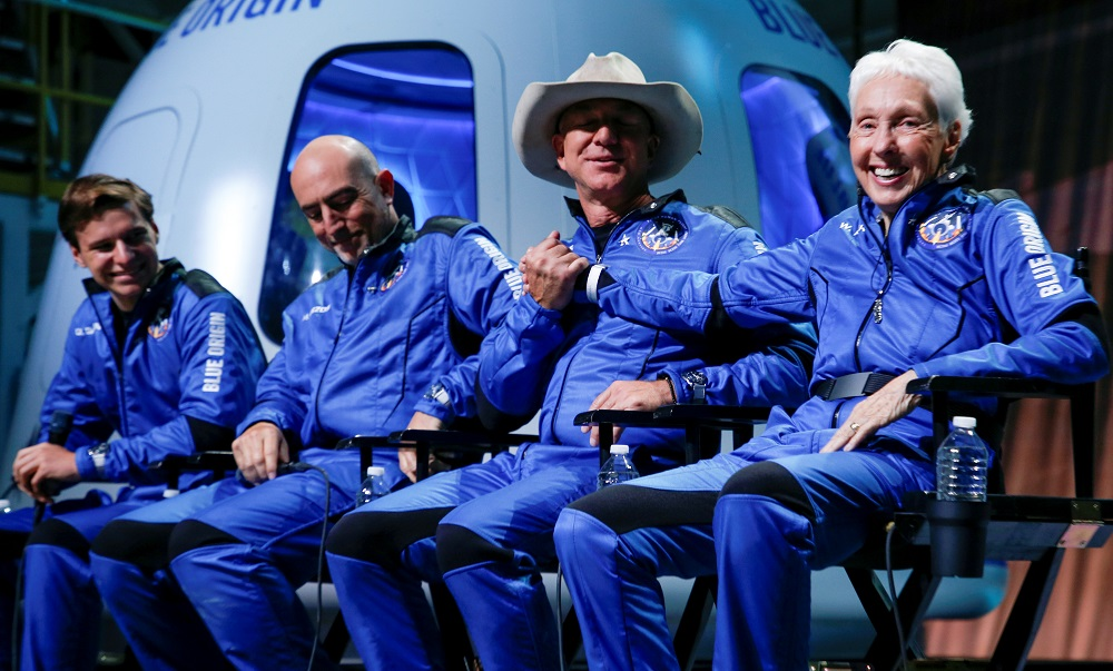 Billionaire American businessman Jeff Bezos (third left) shakes hands with Wally Funk, who became the oldest person in space with other crew mates Oliver Daemen (left) and Mark Bezos (second left) at a post-launch press conference after they flew on Blue Origin's inaugural flight to the edge of space, in the nearby town of Van Horn, Texas July 20, 2021. — Reuters pic
