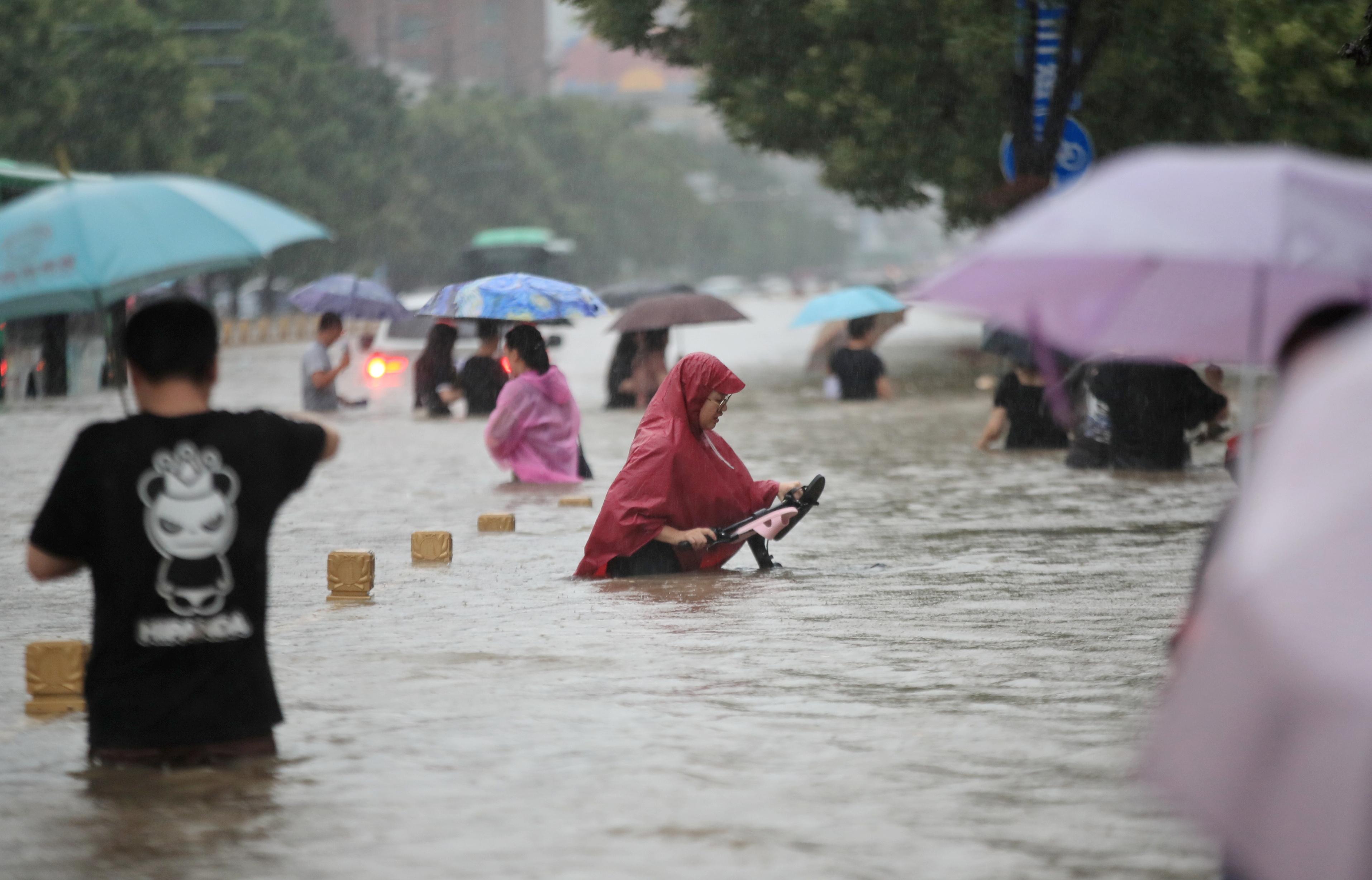 周二傍晚下班时分,河南郑州市民暴雨中相互搀扶踏上回家路。图为市民在积水中趟行。-路透社-