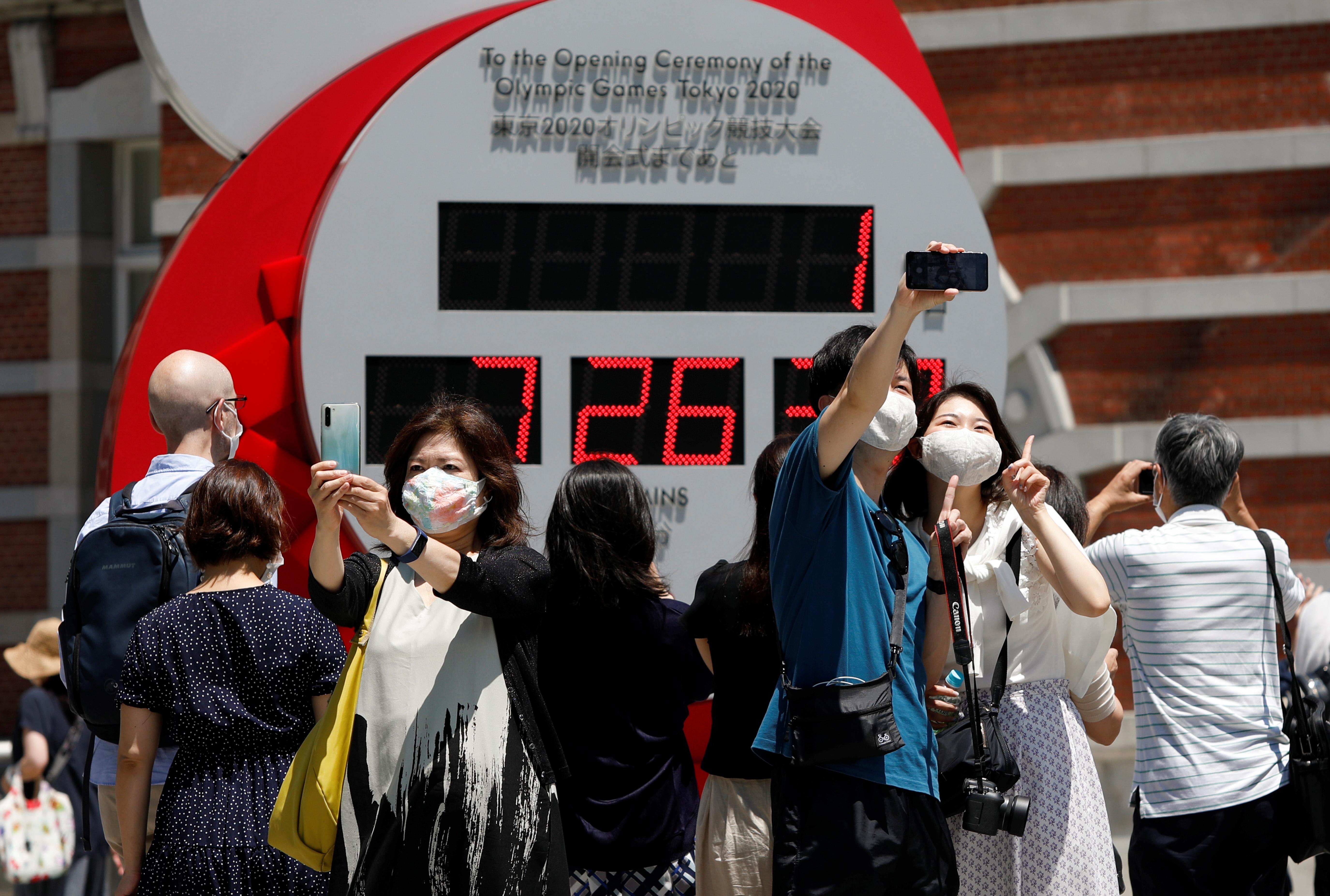 东京奥运会开幕前夕,人们到东京车站外的奥运会倒计时钟前拍照留念。-路透社-