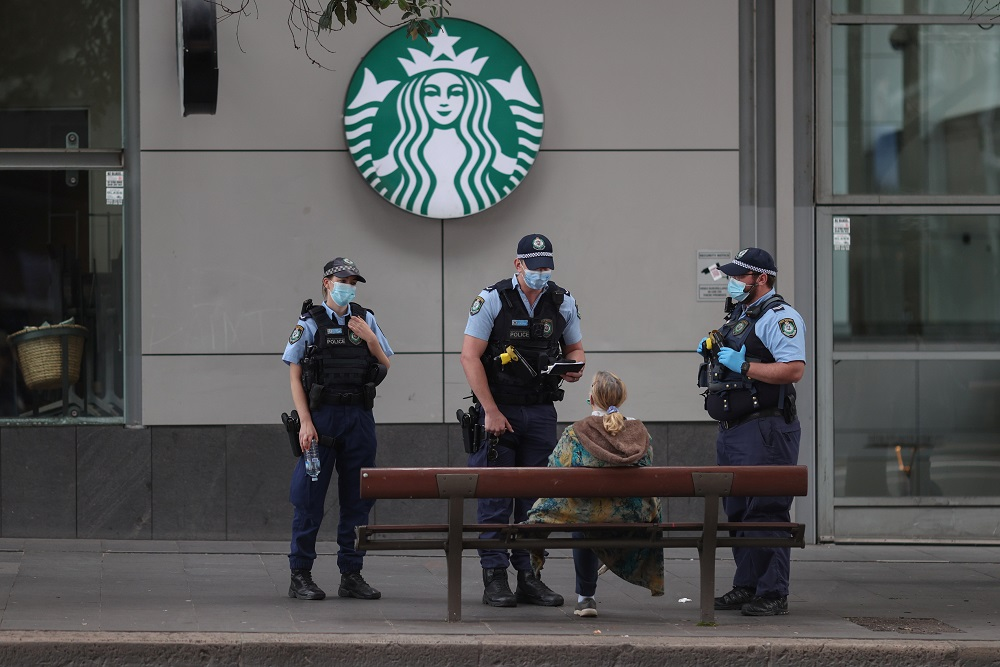 Police officers check the identification of men in the city centre during a law enforcement operation to prevent anti-lockdown protesters from gathering during a Covid-19 lockdown in Sydney July 31, 2021. — Reuters pic